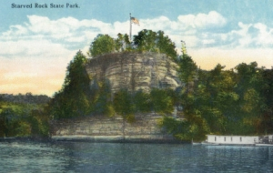 This image, from a vintage postcard, shows Starved Rock at it's summer best. The white sandstone rock soars high above the Illinois River, which washes its base.